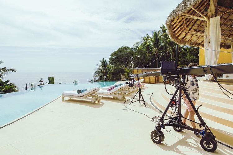 Camera On Crane Poolside With Calm Sea In Background