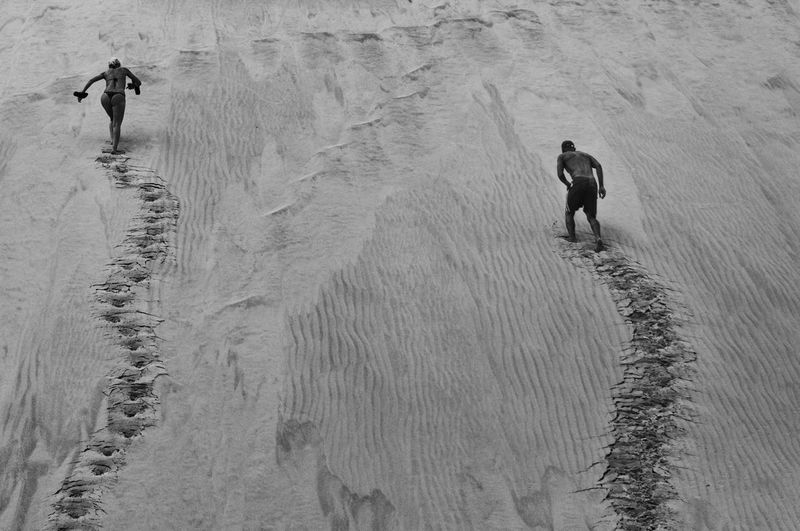 Rear view of man and woman running up a dune