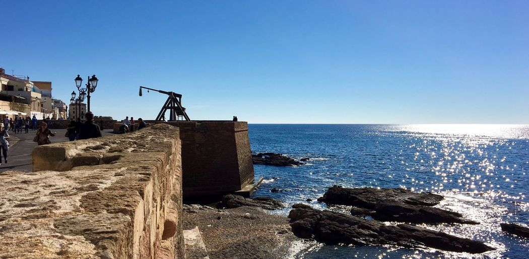 Sea Clear Sky Horizon Over Water Sunlight Water Sky Rock - Object Day Outdoors Blue Built Structure Medieval Streetphotography Alghero Mediterranean  Sardegna Old Architecture Sunlight Tourism Travel Destinations Town