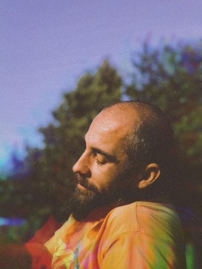 Portrait of man looking away against trees
