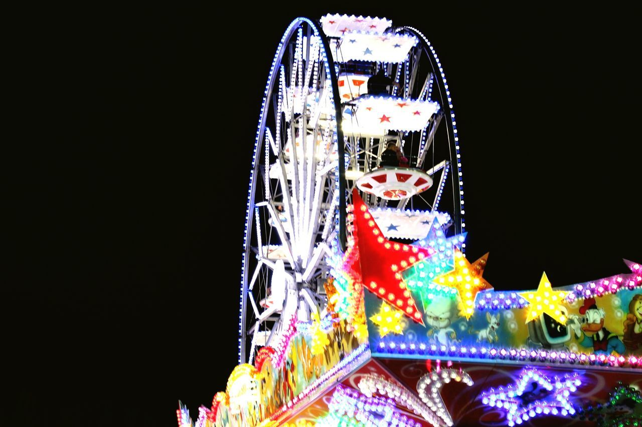 amusement park, arts culture and entertainment, amusement park ride, night, carousel, ferris wheel, illuminated, black background, animal representation, no people, multi colored, clear sky, outdoors, ride, low angle view, motion, merry-go-round, sky