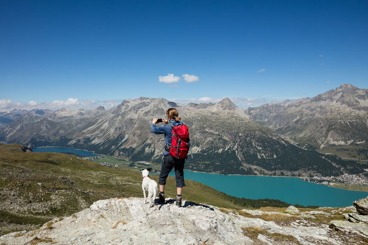 Woman With Dog Photographing Through Mobile Phone While Standing On Mountain Against Sky