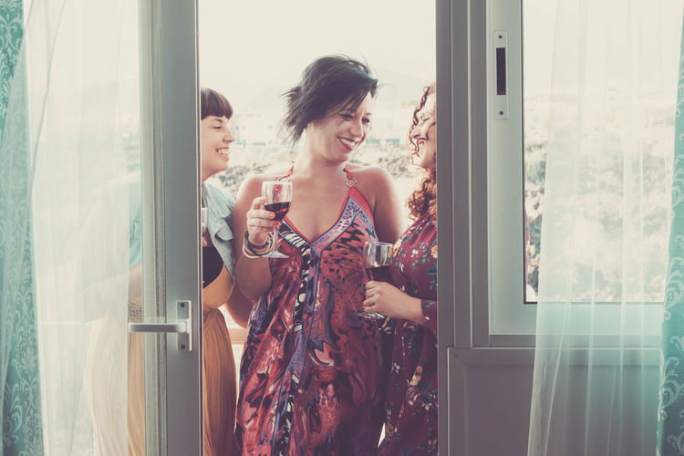 Smiling friends holding wineglasses seen through doorway