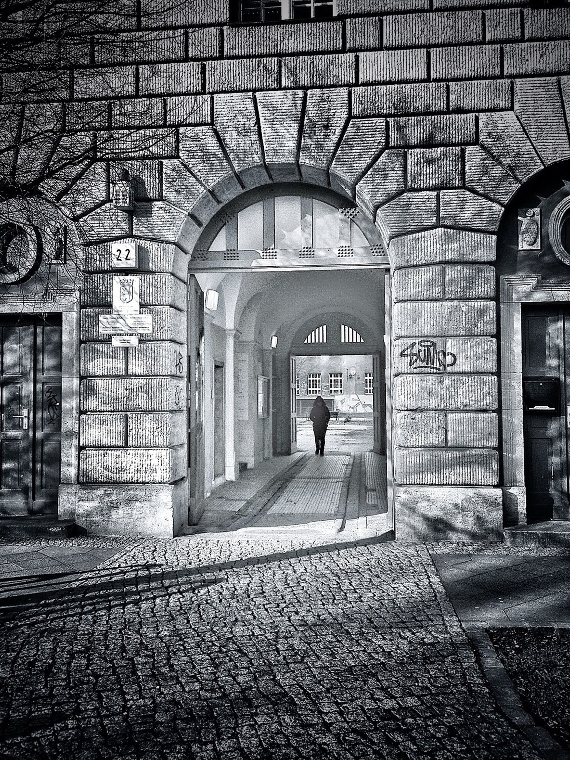 architecture, built structure, arch, building exterior, walking, full length, men, brick wall, entrance, lifestyles, wall - building feature, building, cobblestone, archway, rear view, stone wall, door, day