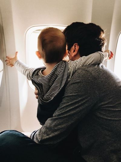 Closeness Hug Family Air Travel  Traveling Father & Son Natural Light Airplane Window Toddler  Lifestyles Togetherness Real People Sitting Two People Positive Emotion Happiness Relaxation Bonding