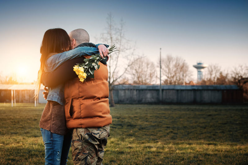 Women's Day Adult Affectionate Arm Around Bonding Casual Clothing Couple - Relationship Embracing Emotion Flower Focus On Foreground Heterosexual Couple Love Males  Men Outdoors People Positive Emotion Rear View Romance Rosé Standing Togetherness Two People Women Yellow