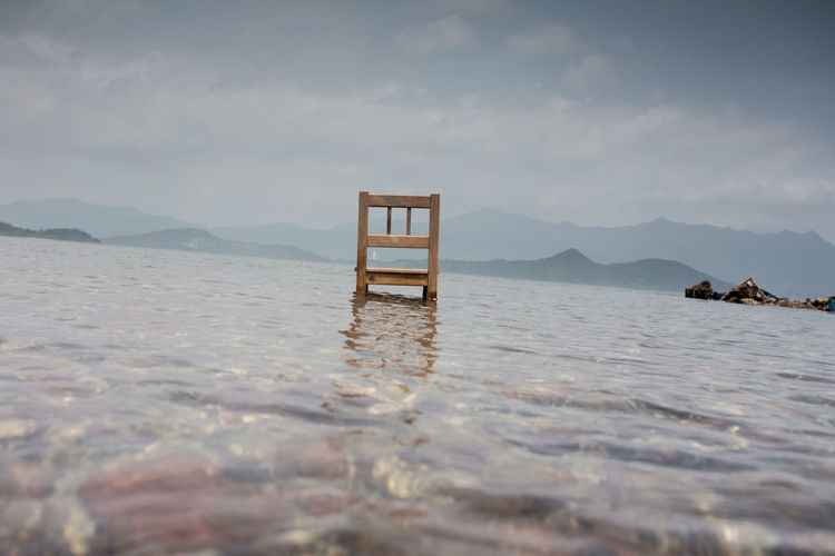 Abandoned chair in lake against sky