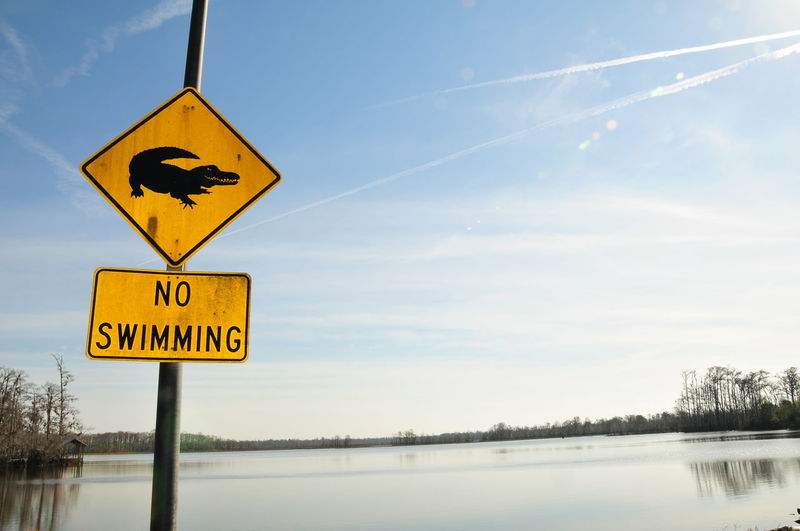 No Swimming Sign By Lake Against Sky