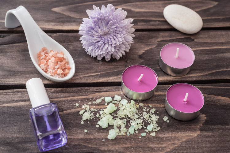 Close-up of beauty products and candles on table