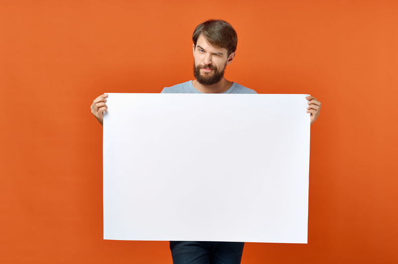 Portrait of young man standing against orange background