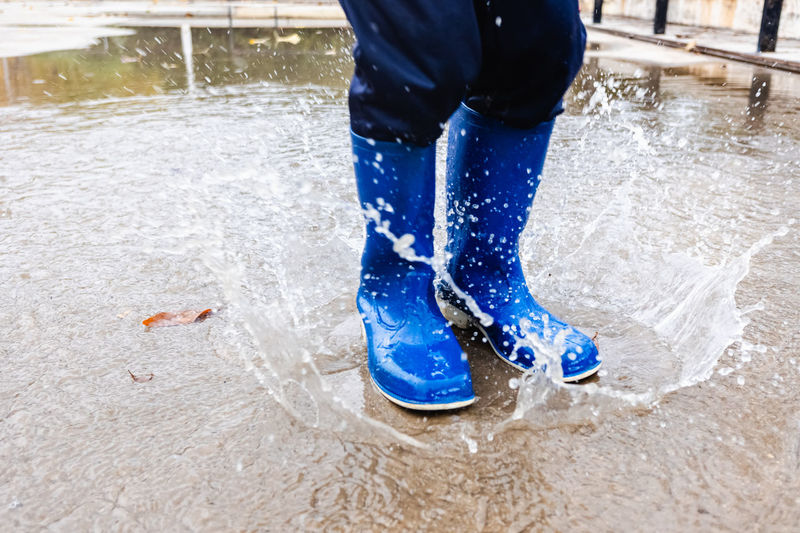 Low section of person splashing puddle water during rainy season