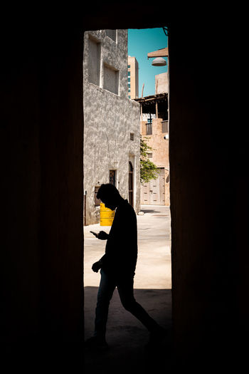Side view of silhouette woman standing against building