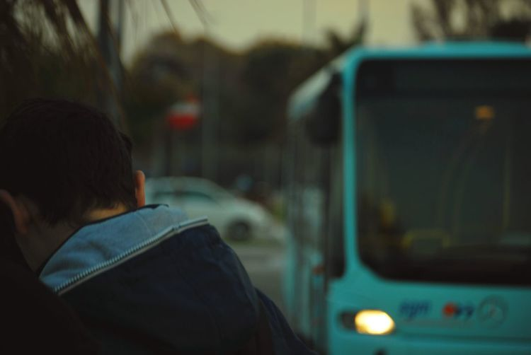 Rear View Of Man By Bus On Street At Dusk