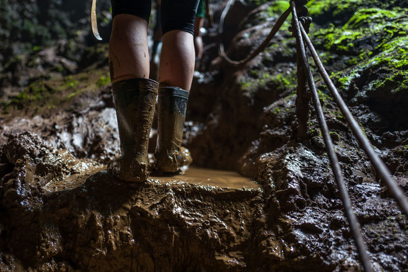 Low section of woman wearing muddy rubber boots while standing on rock in forest