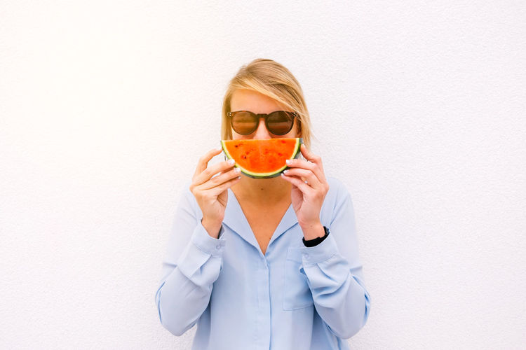 portrait of a young woman holding a slice of watermelon against white background Watermelon Woman Girl Food Beautiful Eating Happy Young Adult Summer Smile Pretty People Fruit Healthy Eating Backgrounds White SLICE Portrait Isolated Freshness Diet Ealthy Smiling Blouse Tasty Sweet Sunglasses Lifestyles Blond Hair Caucasian Fashion Females Cute Cheerful Color Cool Hot Spring Day Daylight Real People Juicy Holiday Vacations One Person Front View Holding Looking At Camera White Background Glasses Hair Standing Women Copy Space Indoors  Wall - Building Feature Obscured Face Beautiful Woman Hairstyle