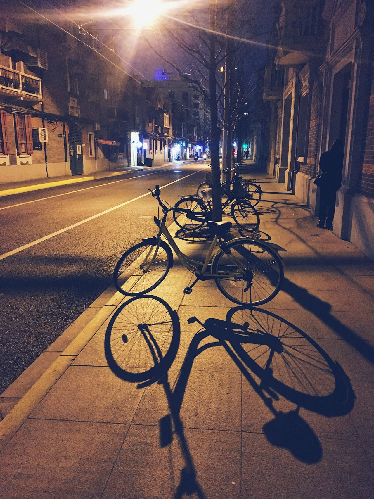 Bicycled parked on sidewalk at night