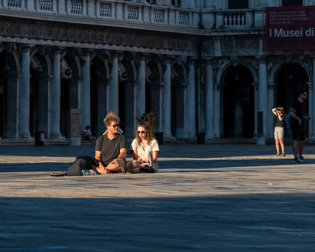 Young couple sitting on historical building