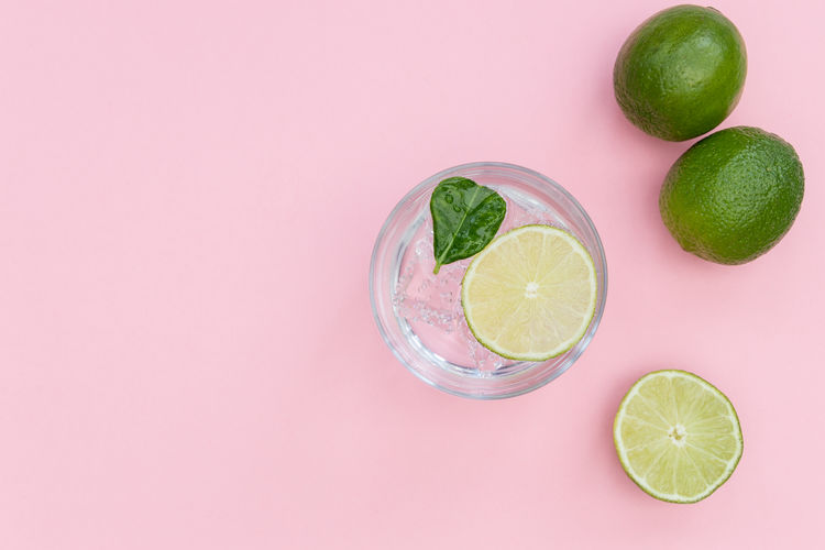 GIN Tonic Cocktail Drink Glass Ice Cold Pink Background Minimal Summer Top View Overhead Above Flat Lay Lime Green Lemon Cucumber Juniper Berries Alcohol SLICE Fruit Botanical Beverage Leaf Color Refreshment Mint Rhubarb Bubbles Sparkling