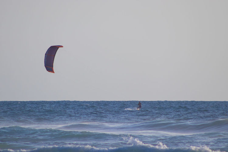 Person paragliding in sea against clear sky