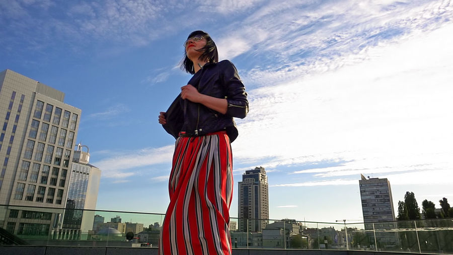 Low angle view of woman standing in city against sky