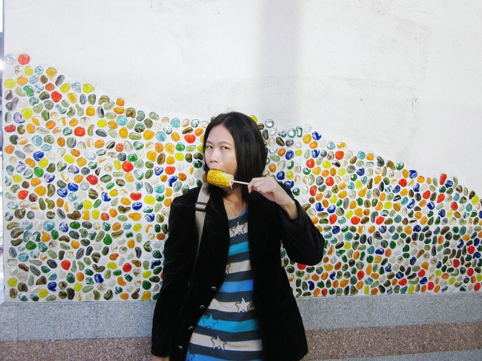 Portrait of woman eating sweetcorn while standing against multi colored wall