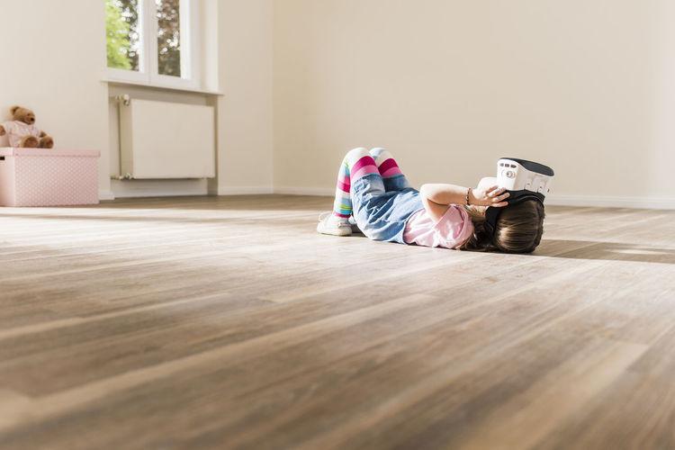 Boy sitting on hardwood floor at home