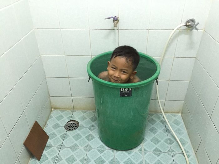 Happy boy in bucket in bathroom