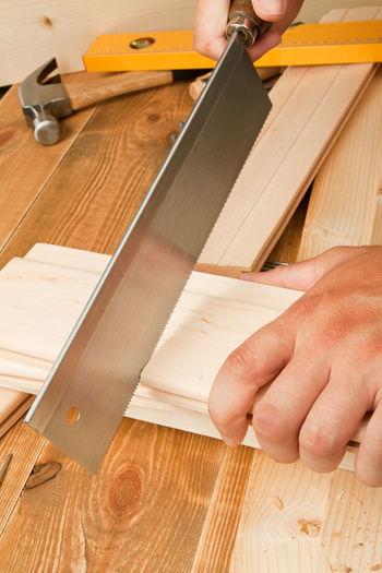 Close-Up Of Carpenter Cutting Wood
