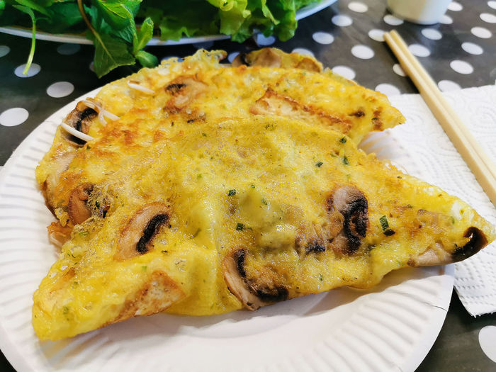 Vietnamese fried pancake made of rice flour and on table with lettuce and aromatic herbs
