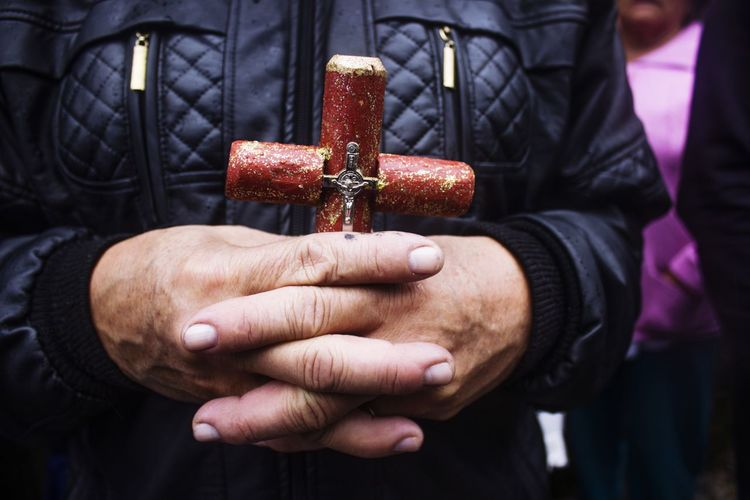 Close-up of man holding religious cross