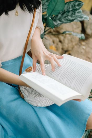 Midsection of woman reading book while sitting outdoors