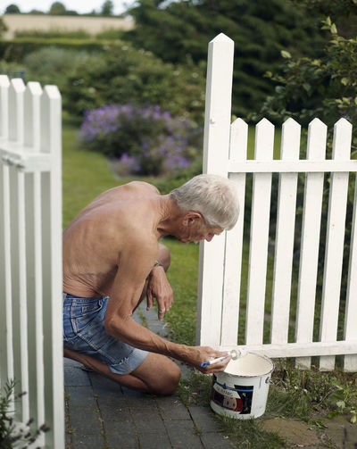 Side view of man climbing on chair in yard