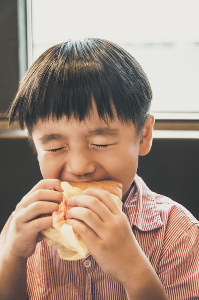 Portrait of a young Asian boy eating yummy burger with oozing facial expression 5 Years Old Asian  Boy Burger Casual Clothing Child Childhood Delicious Eating Everyday Emotion Eyes Closed  Facial Expression Fast Food Holding Indoors  Kid Lifestyles Natural Light Oozing People Portrait Tasty Vertical Composition Young YummyThe Portraitist - 2016 EyeEm Awards The Portraitist - 2017 EyeEm Awards