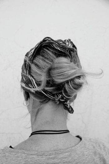 Rear view of mature woman with blond hair standing against wall