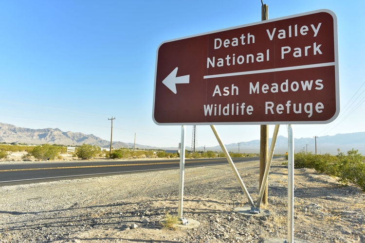 Death valley national park sign on field by road against clear blue sky