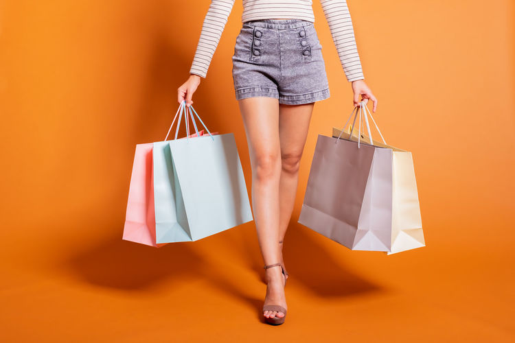 Low section of woman with shopping bags standing against orange background