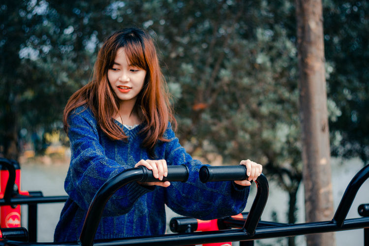 Exercise for beauty One Person Hair Long Hair Hairstyle Focus On Foreground Young Adult Sitting Adult Waist Up Transportation Day Women Brown Hair Front View Beauty Medium-length Hair Portrait Beautiful Woman Outdoors Bangs