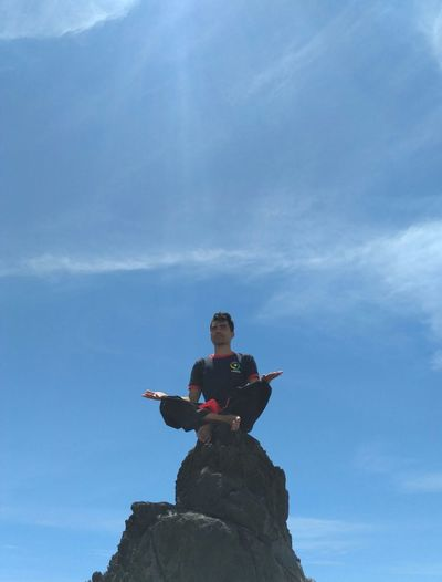 Low angle view of woman mediating while sitting on rock against sky