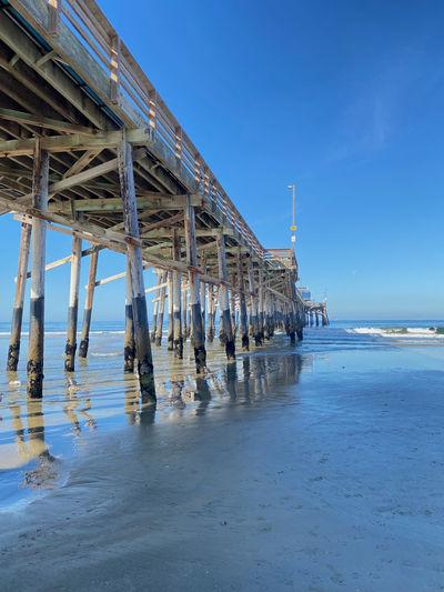 Pier on beach against blue sky