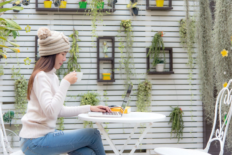 Midsection of woman holding food while sitting outdoors