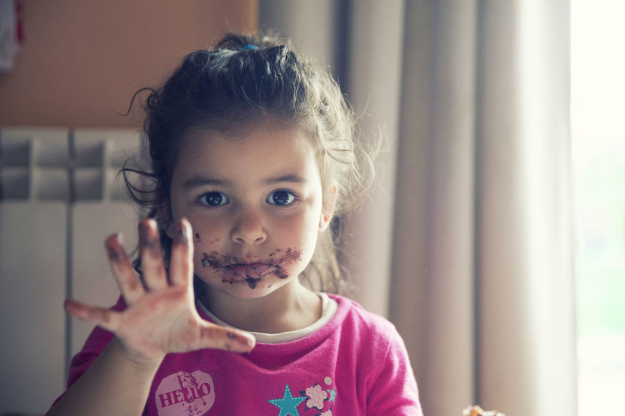 Girl and dirty chocolate mouth Child Childhood Chocolate Cute Dirty Mouth Elementary Age Front View Girls Headshot Home Interior Indoors  Innocence Leisure Activity Lifestyles Looking At Camera One Person Portrait Real People