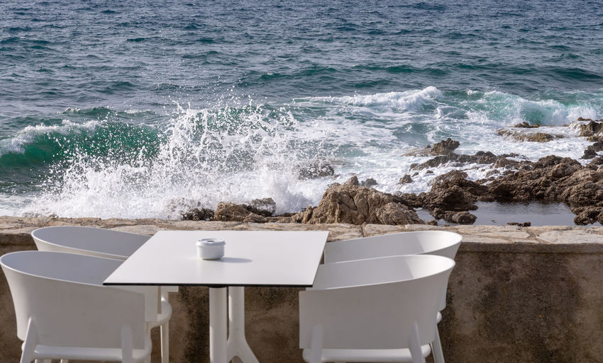 Empty Table And Chairs Against Waves Splashing On Rocks In Sea
