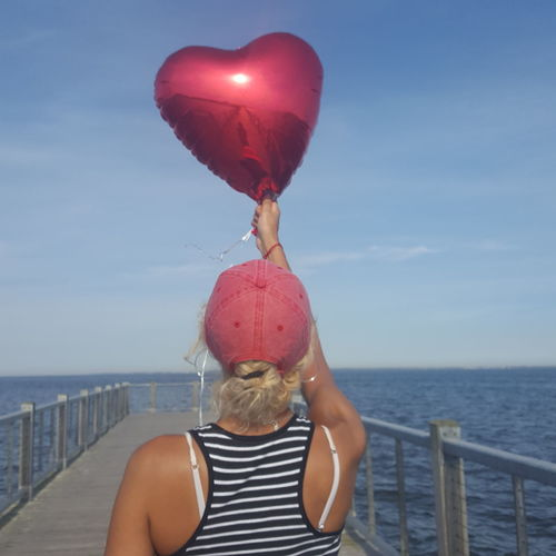 Rear view of woman with balloons against sea against sky