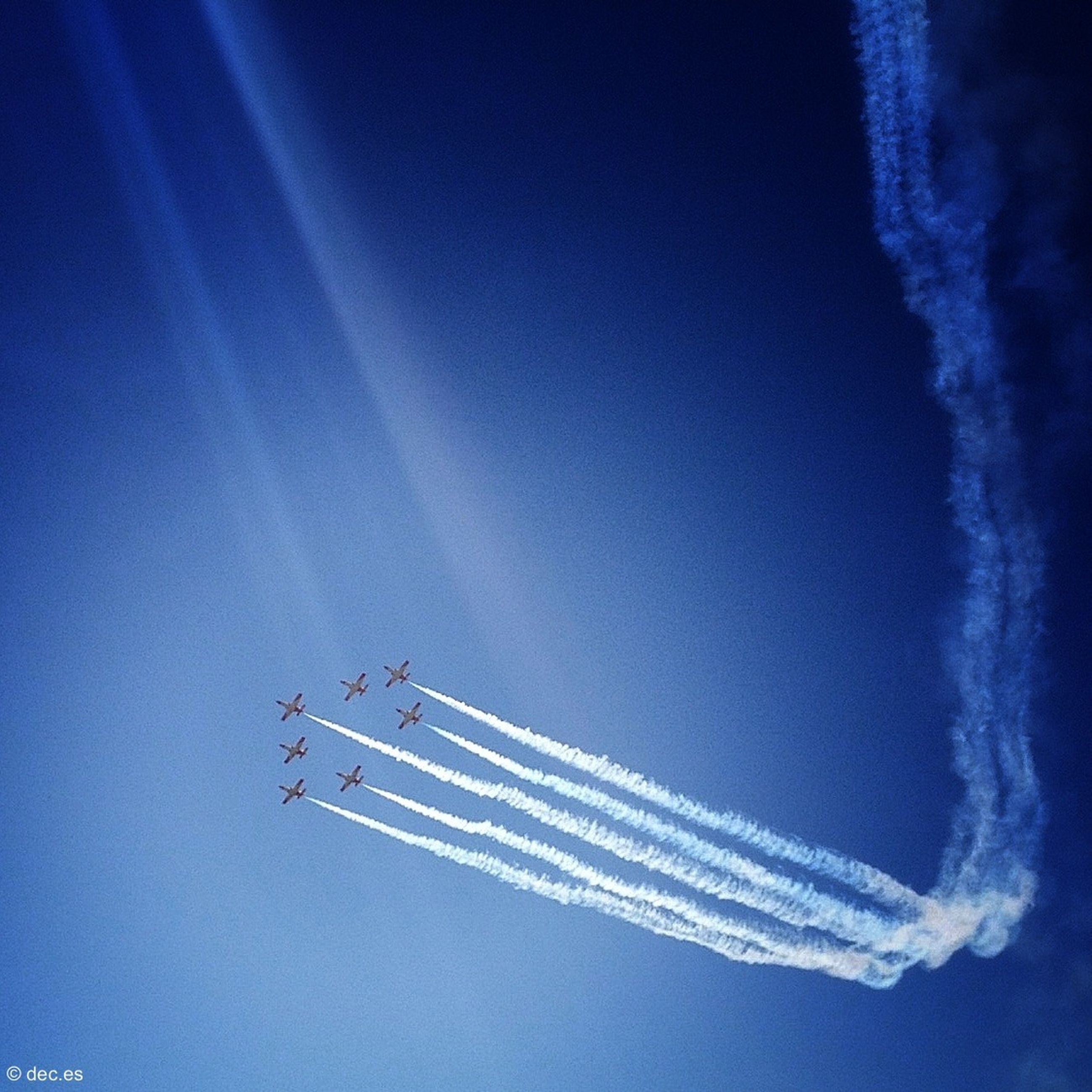 blue, low angle view, sky, vapor trail, air vehicle, airplane, transportation, clear sky, copy space, mode of transport, flying, outdoors, no people, smoke - physical structure, travel, day, nature, motion, speed, cloud - sky