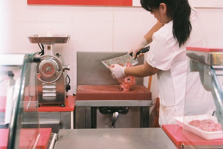 Rear View Of Butcher Slicing Meat In Shop