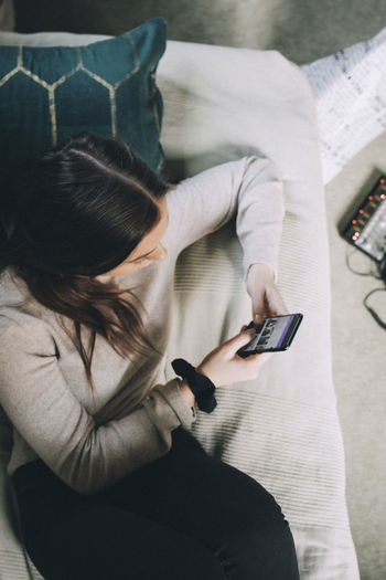 High angle view of woman using mobile phone while sitting on sofa