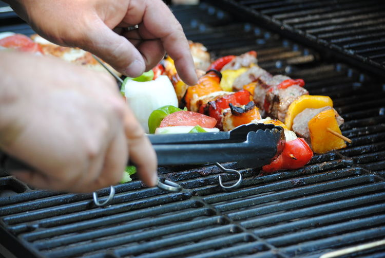 Cropped hand holding serving tongs by food in skewers on barbecue grill