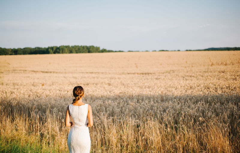 Rear view of bride standing on farm