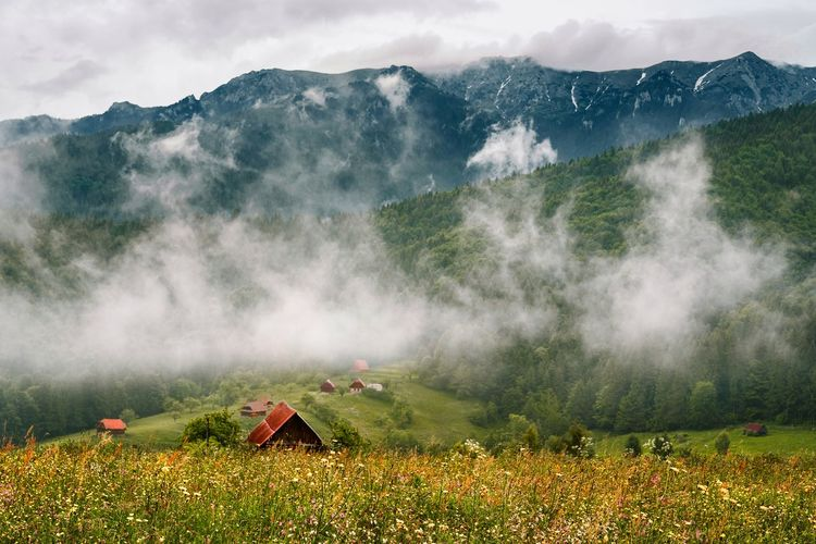 Scenic view of village against mountain against cloudy sky