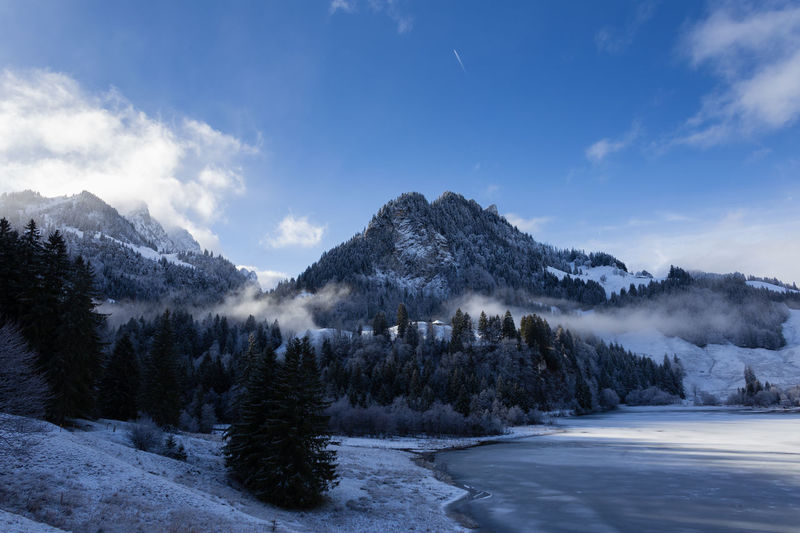 Shadowplay at frozen lake Alps Switzerland Blue Sky Clouds And Sky Frozen Lake Lake View Lakeside Morning Mountainview Nature Outdoor Photography Outdoors Scenics Schwarzsee Shadowplay Snow Trees White Winter